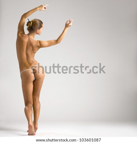 Beautiful naked body of young and sexy woman standing near the white wall - stock photo