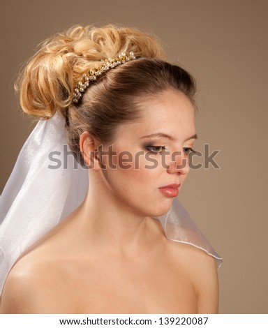 Beautiful  naked bride with hairstyle looking down - stock photo