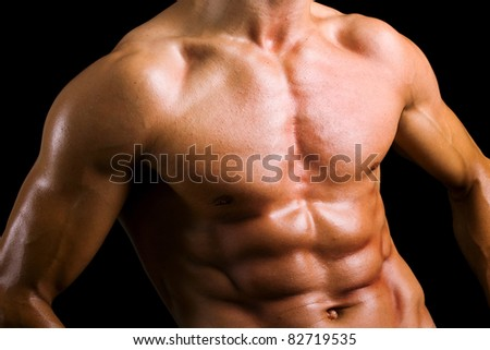 Beautiful naked male torso against black background - stock photo