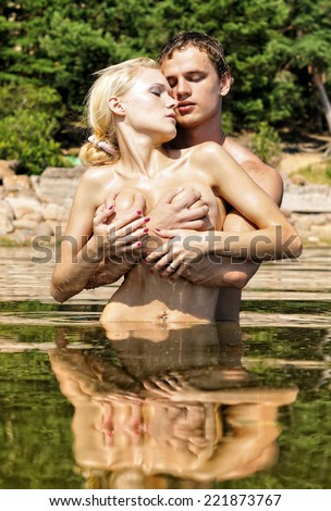 Beautiful naked man and woman kissing in the water outdoors. - stock photo