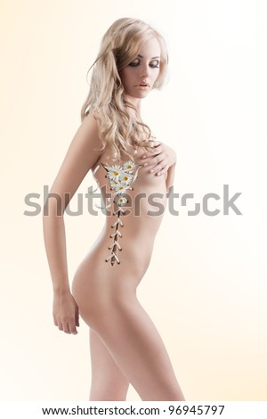 beautiful naked sexy woman in a creative shot with her body open like a corset and leaves coming out - stock photo