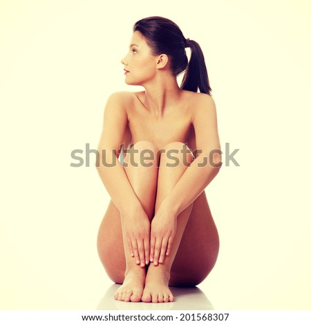 Beautiful naked woman sitting on flor - stock photo