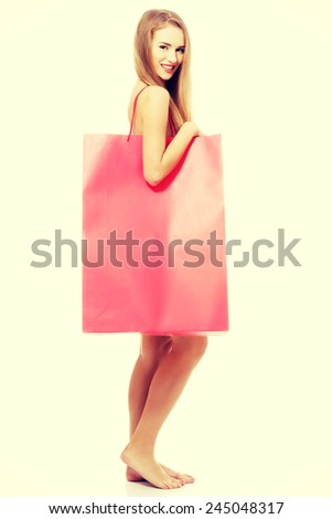 Beautiful naked woman with big red shopping bag. - stock photo