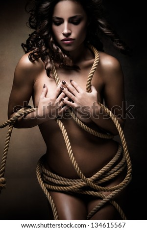 beautiful naked young woman with a rope around the body, studio shot - stock photo