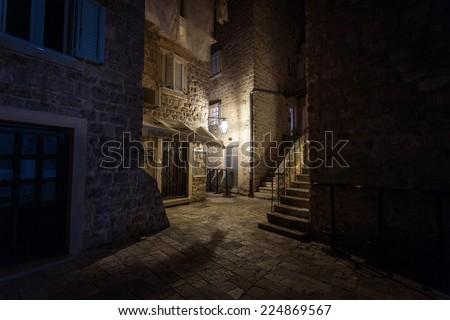Beautiful narrow street of ancient city illuminated by lantern at night - stock photo