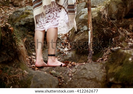 beautiful native indian american woman legs with pikestaff walking on background of woods - stock photo