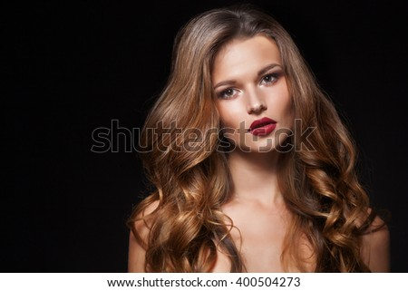 Beautiful natural curly blonde hair, portrait of an young girl isolated on black - stock photo