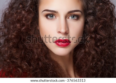 Beautiful natural curly brunette hair, portrait of an young girl with red lips - stock photo