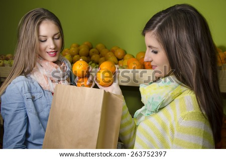Beautiful natural girls buying oranges in fruit market, selective focus on oranges  - stock photo