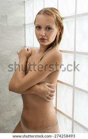 Beautiful, natural, nude, fresh blonde woman under the shower her body is wet and she is covering her breast by arms. - stock photo
