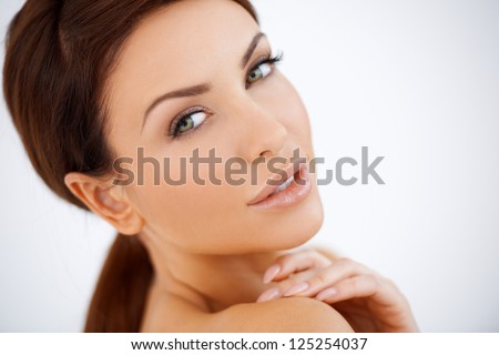 Beautiful natural sensual woman posing looking over her shoulder at the camera with a seductive look, studio portrait with bare shoulders - stock photo