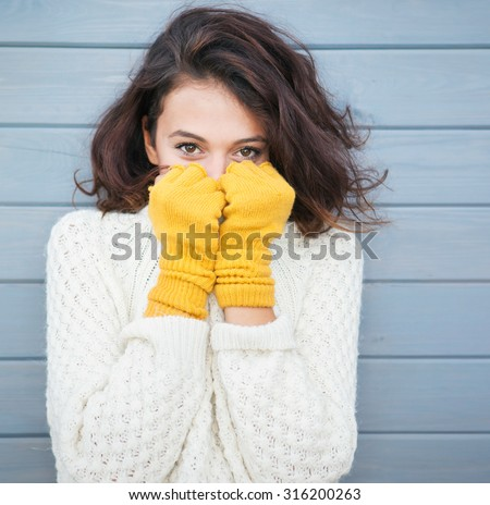 Beautiful natural young smiling brunette woman wearing knitted sweater and gloves. Fall and winter fashion concept. - stock photo