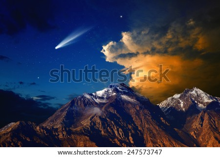 Beautiful nature background - bright comet in dark blue sky with stars, mountain with snowy peaks, red light from sunset illuminates mountains, glowing clouds - stock photo