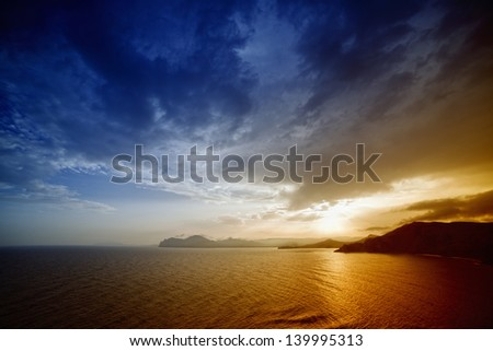 Beautiful nature background - sunset over sea and mountains - stock photo