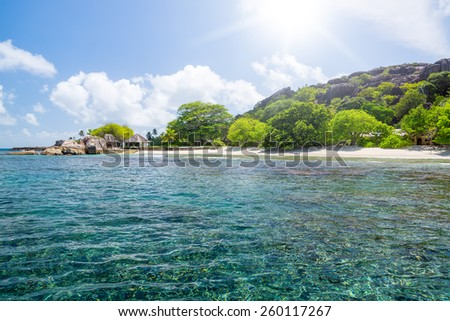 Beautiful nature on the shore of the turquoise waters of the ocean. Surrounded by tropical greenery. The Seychelles. - stock photo