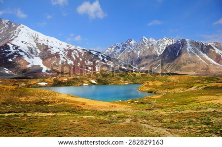 Beautiful nature scenery with bright blue lake in desert valley, mountain range covered with snow against the background of blue sky in Himalaya, Ladakh, Jammu & Kashmir, Northern India, Central Asia - stock photo