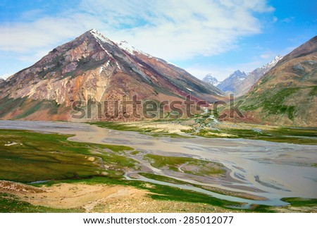 Beautiful nature scenery - Zanskar river against the background of colorful Himalaya mountains covered with snow and blue sky in Ladakh, Jammu & Kashmir, Northern India, Central Asia - stock photo