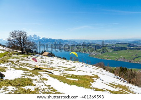 Beautiful nature view in the mountains with people paragliding over the lake - stock photo