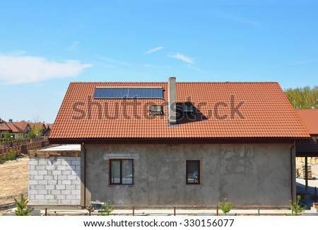 Beautiful New Building House Energy Efficiency Solution Concept Outdoor. Solar Energy, Solar Water Heater, Rain Gutter, Skylights, Installed on Ceramic Red Tiled Roof Exterior. Plastering Facade Wall - stock photo