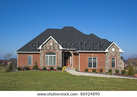 Beautiful new home against a beautiful blue sky, located in affluent neighborhood - stock photo