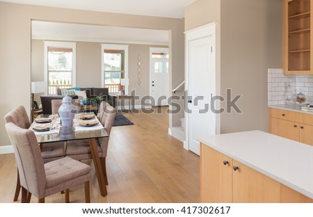 Beautiful new home interior with open floor plan: includes kitchen, dining room, living room, and foyer or entry - stock photo