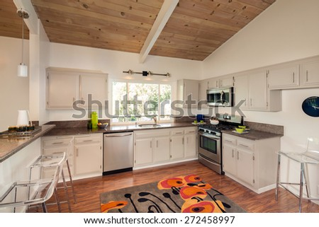 Beautiful New kitchen in mid century home with deep sink, cabinets, cherry wooden floor and wooden ceiling. Stylish new kitchen in white with granite counter tops with stainless steel oven and stove. - stock photo