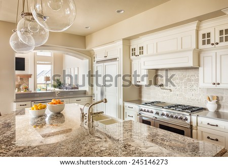 Beautiful New Kitchen Interior with Island, Sink, Cabinets and Pendant Lights in New Home - stock photo