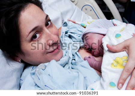 Beautiful new mother happy holding her infant baby after giving birth in hospital. - stock photo