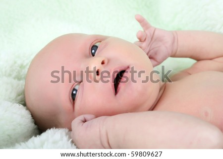 Beautiful newborn baby girl lying on a soft green blanket - stock photo