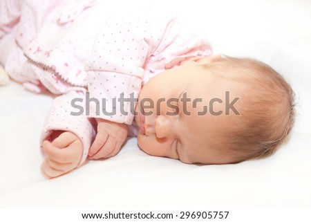 Beautiful newborn baby is sleeping on a white bed - stock photo