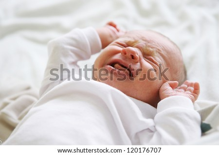 Beautiful newborn baby lying in his bed - stock photo