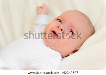 Beautiful newborn baby lying in his bed - stock photo