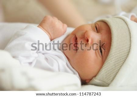 Beautiful newborn baby wake up in his bed - stock photo