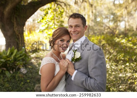 Beautiful newly married couple together in garden - stock photo