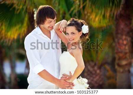 beautiful newlywed couple on a background of tropical trees. newly married celebrating their honeymoon - stock photo