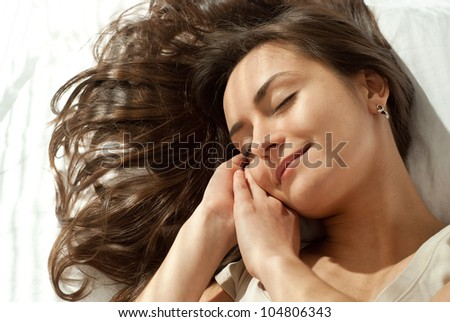 Beautiful nice woman lying on a pillow on a light background - stock photo
