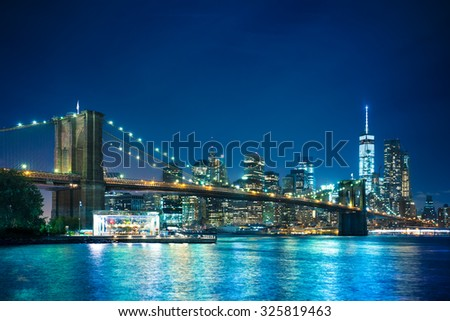 Beautiful night scene of New York City and Brooklyn Bridge looking toward Manhattan - stock photo