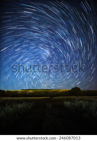 beautiful night sky, spiral star trails and the forest - stock photo
