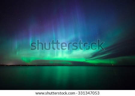 Beautiful northern lights aurora borealis over lake in finland - stock photo
