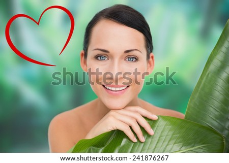 Beautiful nude brunette posing with green leaves against heart - stock photo
