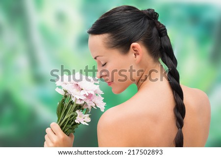 Beautiful nude brunette smelling bunch of pink flowers on blue and green background - stock photo