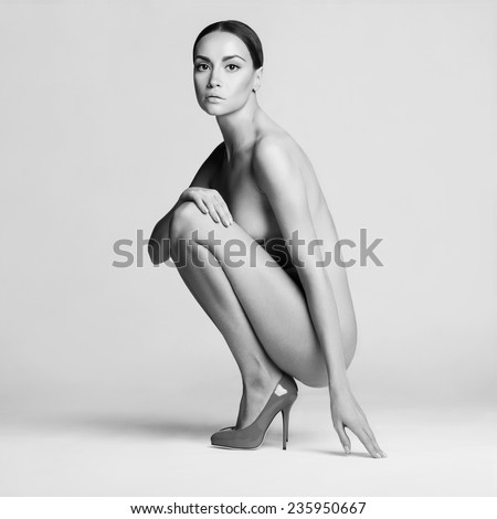 beautiful nude lady with perfect body sits in red shoes. Conceptual fashion art photo - stock photo