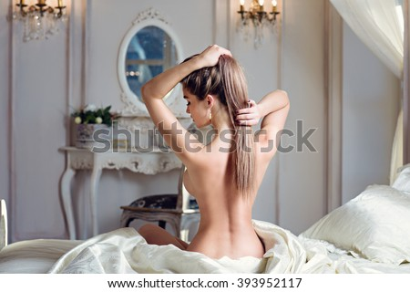 Beautiful nude sexy lady in elegant pose. Portrait of fashion model girl indoors. Beauty blonde woman with attractive buttocks. Close-up female ass and naked body - stock photo