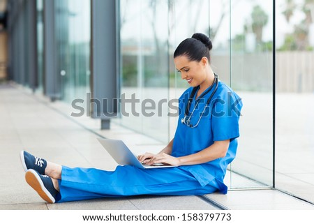 beautiful nurse sitting on floor and using laptop computer during break - stock photo