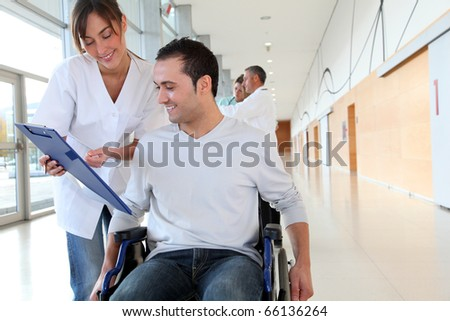 Beautiful nurse standing by man in wheelchair - stock photo