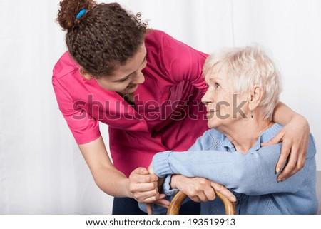 Beautiful nurse taking care of senior woman - stock photo