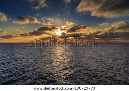 Beautiful ocean sunset with a fiery orange sun backlighting the clouds and casting a reflection over the rippling surface of the water - stock photo