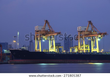 beautiful of container ship in port with lighting and dusky sky background - stock photo