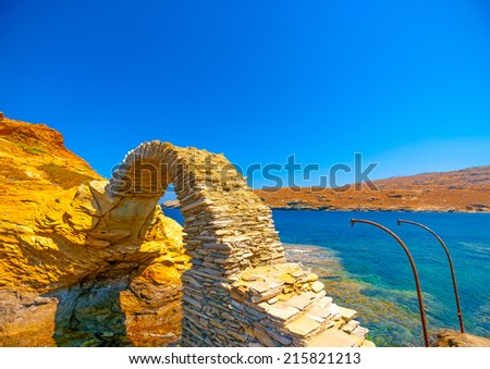 beautiful old bridge made of stone in the sea at Chora, the capital of Andros island in Greece - stock photo