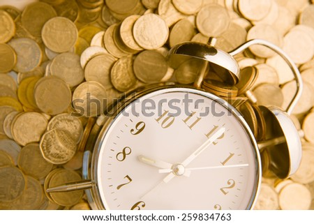 Beautiful old clock staying on one golden coins background. Time is money concept  - stock photo